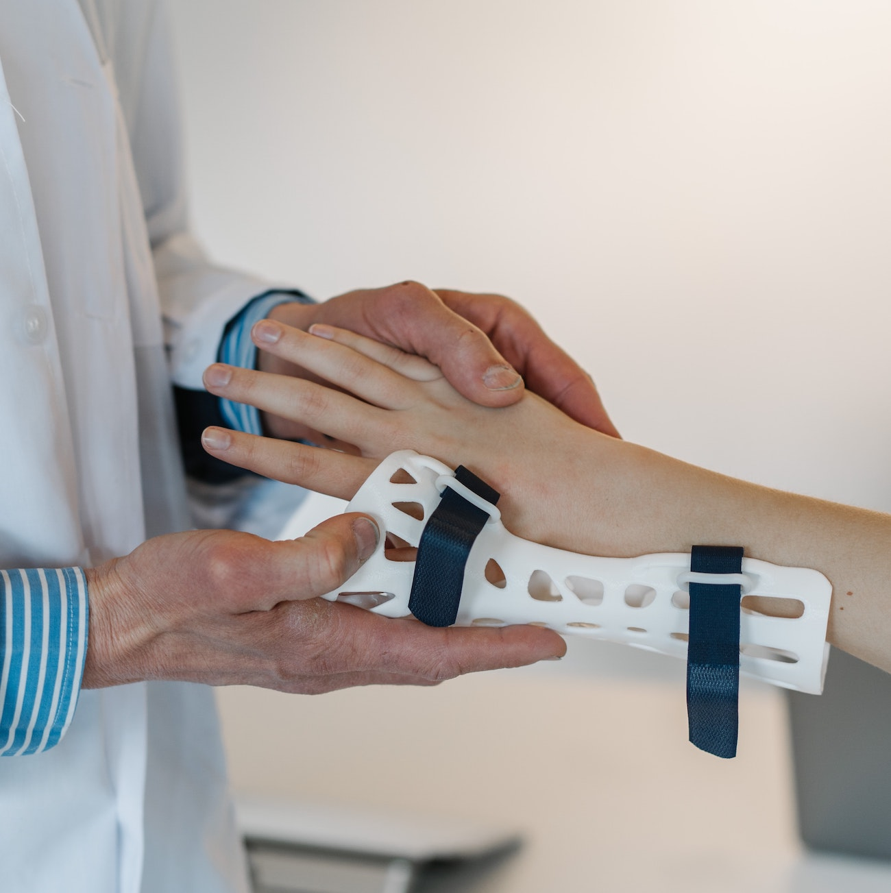 A close-up of a doctor in a white coat putting a brace on a patient's wrist.