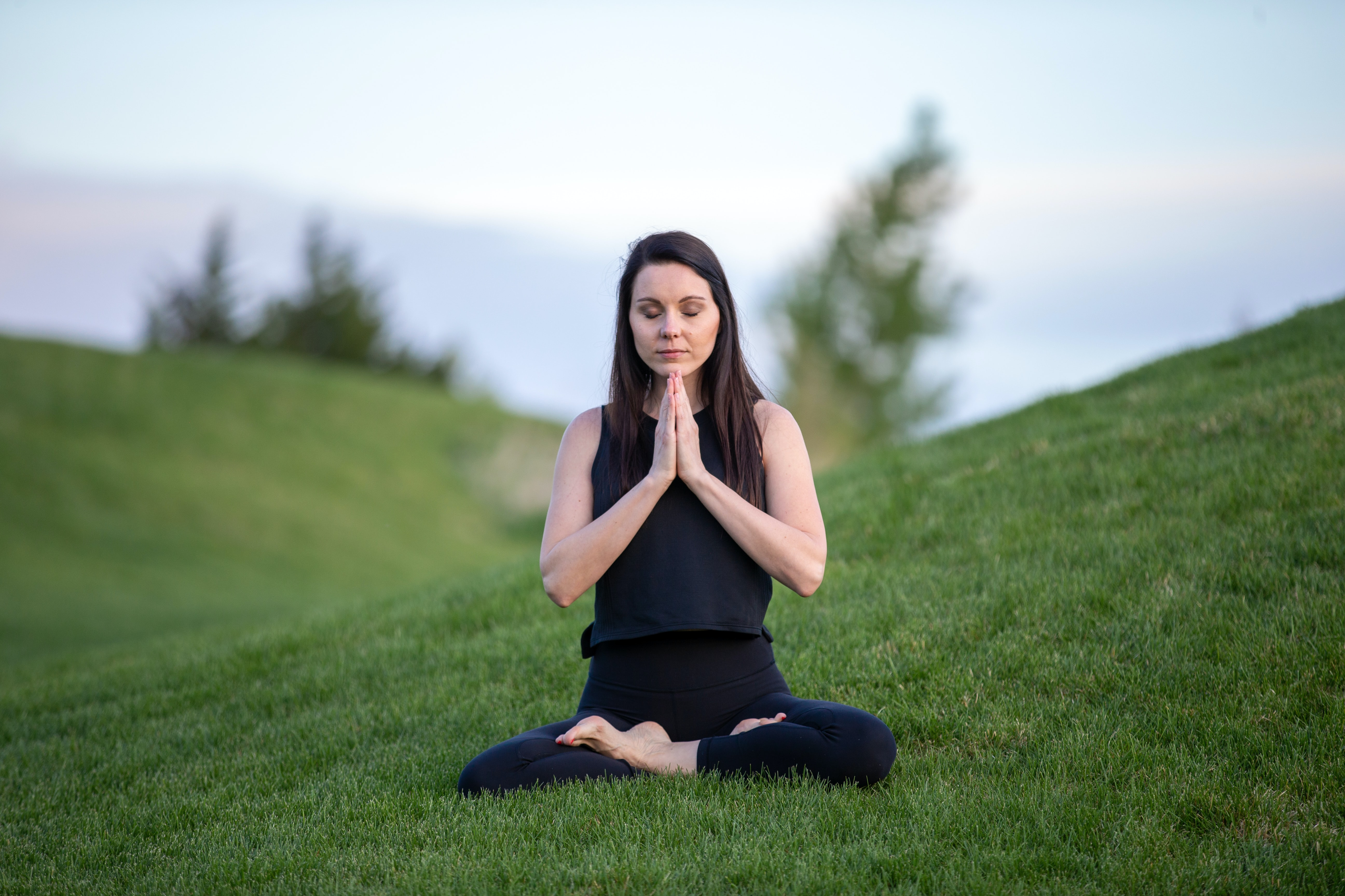 Woman meditating in field with crossed legs and prayer hands.