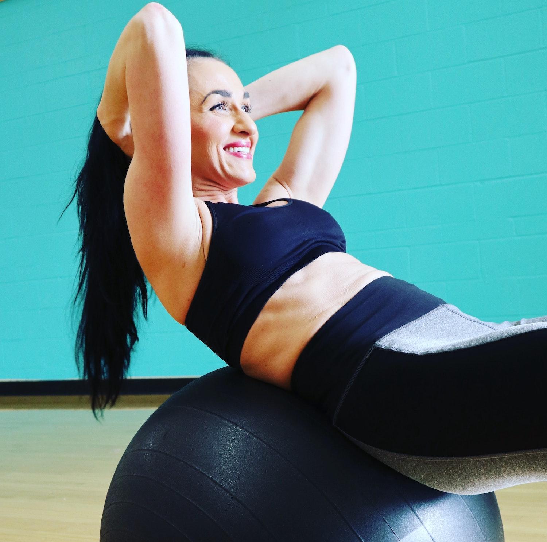 Woman doing ab exercises while balancing on exercise ball.