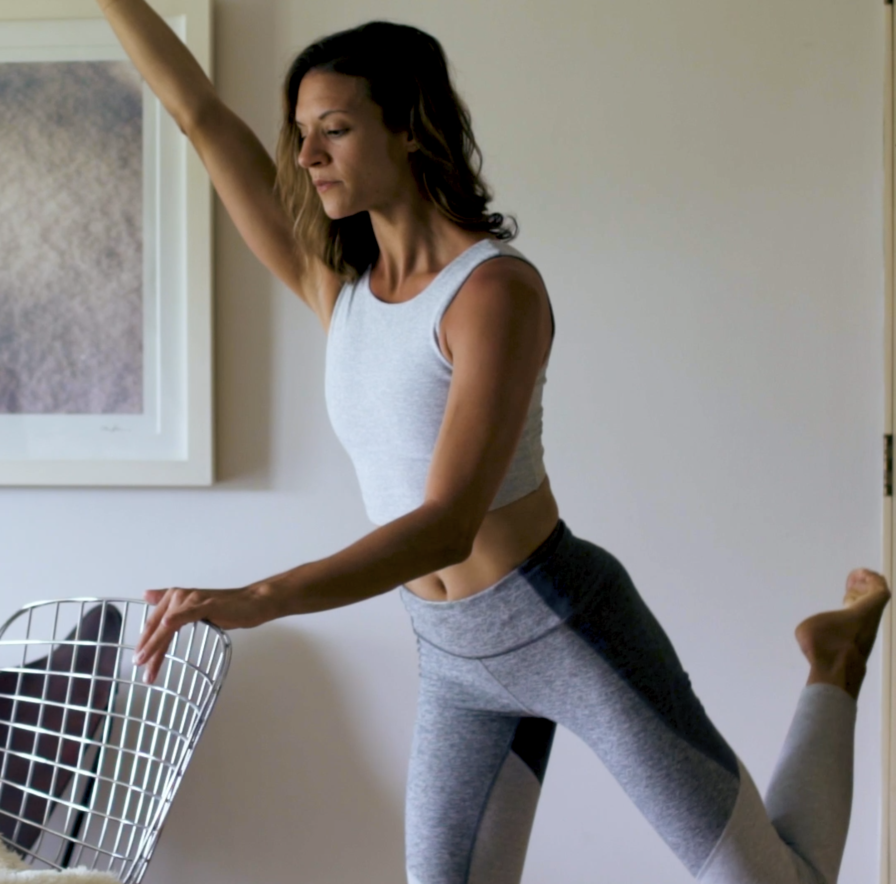 Woman leaning on chair while doing at-home barre exercise.