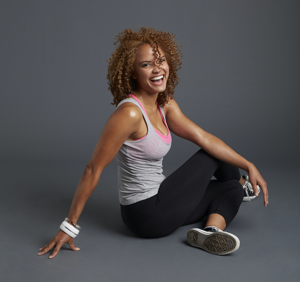 A woman sitting on the floor in workout clothes while smiling at the camera